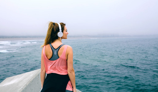 Sportswoman with headphones watching the sea