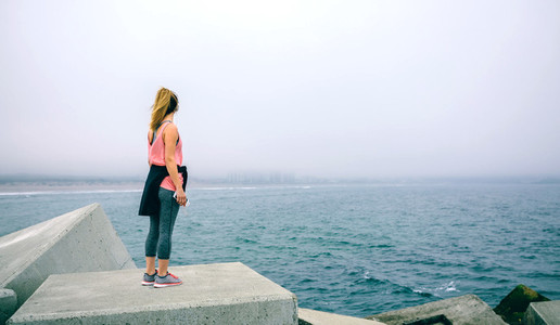 Young woman on concrete block watching the sea
