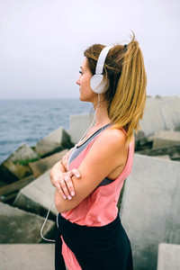 Sportswoman with headphones watching the sea