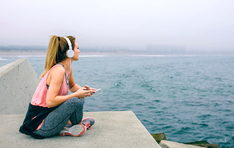 Sitting sportswoman watching the sea