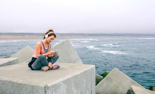 Sportswoman with headphones sitting
