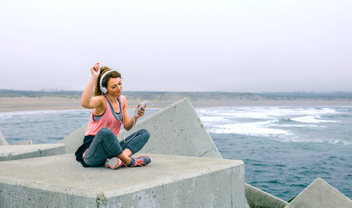Sportswoman with headphones sitting and dancing
