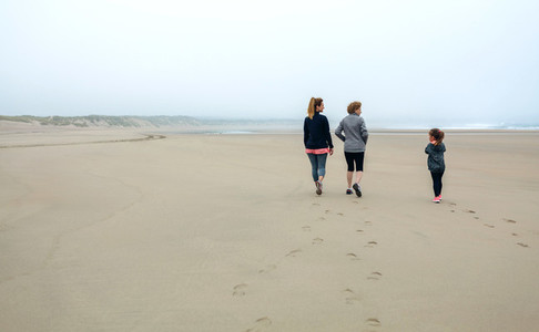 Three generations female walking on the beach