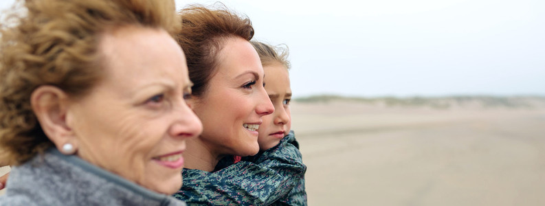 Three generations female looking at sea