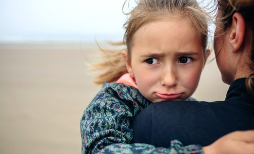 Angry girl hugging her mother on the beach
