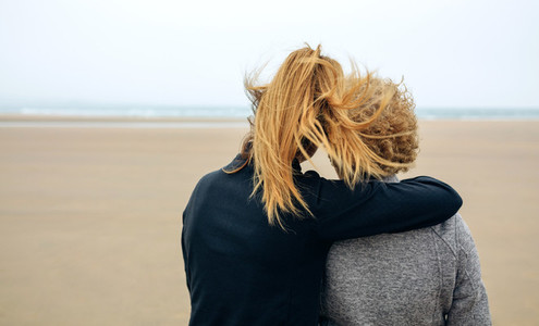 Back view of senior and young woman looking at sea