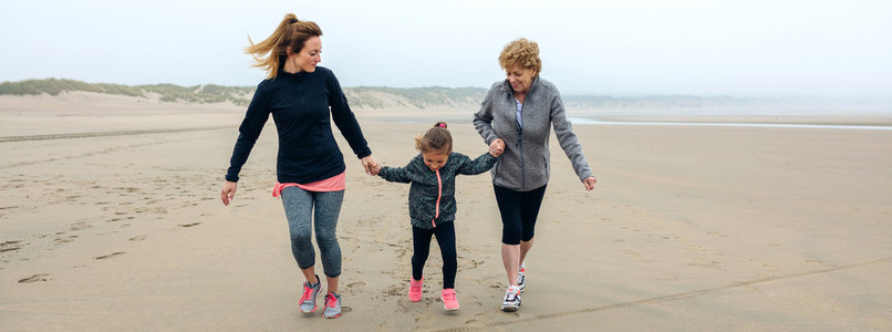 Three generations female running on the beach