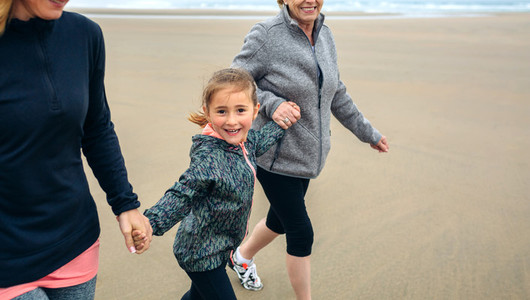 Girl running with two women on the beach