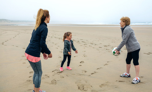 Three generations female playing on the beach