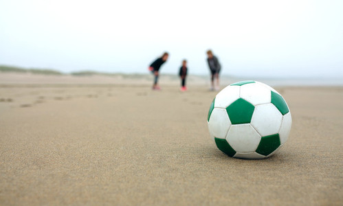 Close up of soccer ball with three people