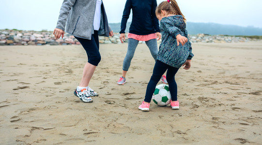 Three generations female playing soccer on the beach