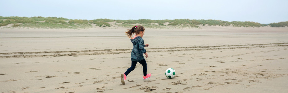 Little girl playing soccer on the beach