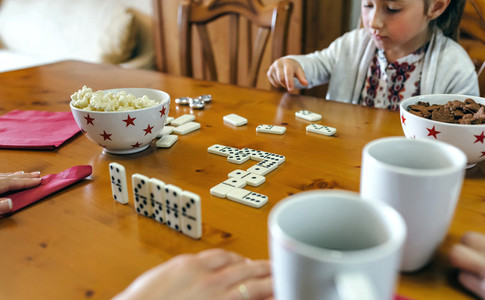 Girl playing domino with her family