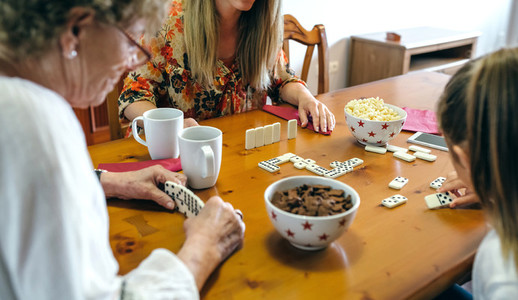 Three female generations playing domino