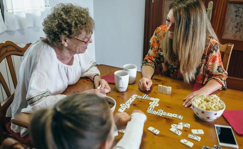 Three female generations playing domino