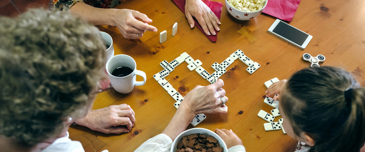 Top view of three female generations playing domino