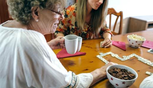 Senior mother and daughter playing domino