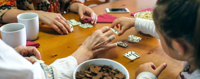 Unrecognizable three female generations playing domino