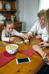 Three female generations playing with dominoes