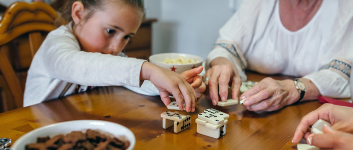 Little girl playing dominoes with mother and grandmother