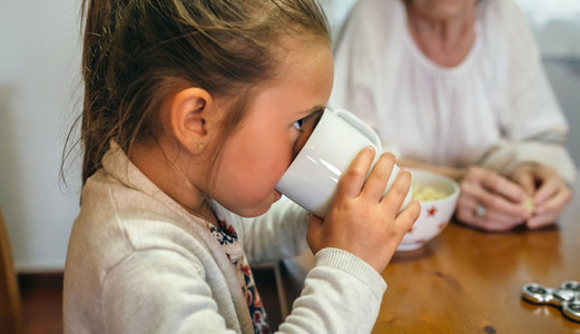 Little girl drinking a cup of milk