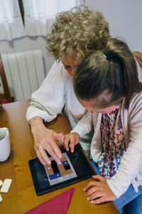 Grandmother and granddaughter playing with tablet