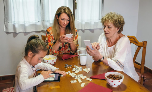 Three female generations using tablet and smartphone