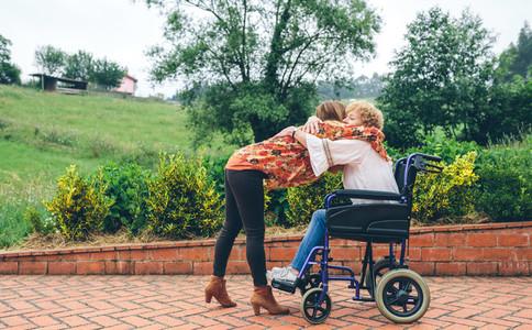 Daughter hugging her senior mother in wheelchair