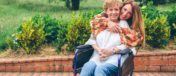 Daughter embracing her senior mother in wheelchair
