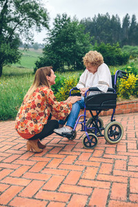 Young woman talking to elderly woman in a wheelchair