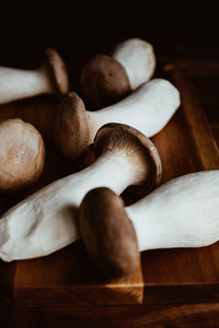 Group of raw King Oyster mushroom also known as eryngii on a wooden cutting kitchen board