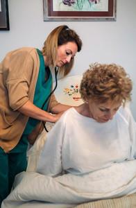 Caregiver auscultating senior woman