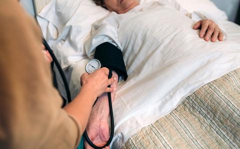 Caregiver checking blood pressure to a senior woman