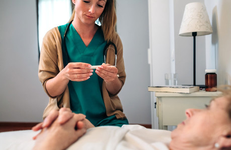 Doctor taking temperature to senior woman