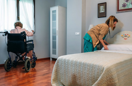 Caregiver making the bed of an elderly patient