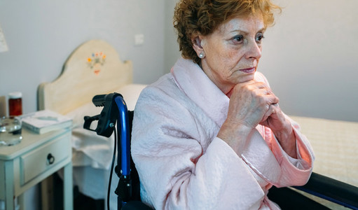 Senior woman in a wheelchair alone