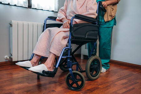 Doctor carrying elderly patient in a wheelchair