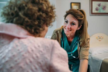 Doctor talking to elderly patient in a wheelchair