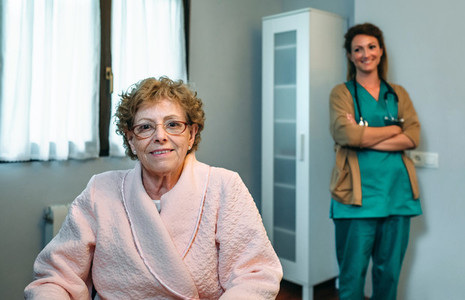 Senior patient posing with doctor in the background