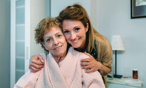 Affectionate caretaker posing with elderly patient
