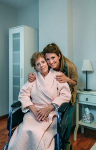 Affectionate caretaker posing with elderly patient