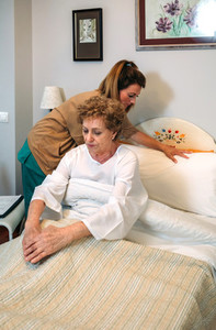 Caregiver accommodating pillow to elderly patient