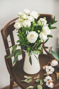 Spring white buttercup flowers in white enamel jug