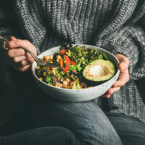 Woman in sweater eating healthy vegetarian dinner square crop
