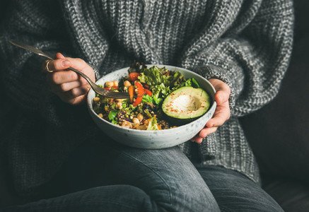 Woman in sweater eating fresh salad  avocado  beans and vegetables