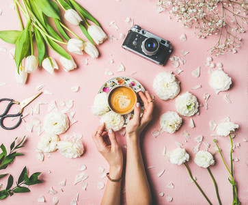 Female hands holding cup of coffee flowers and film camera
