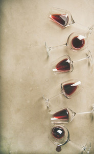 Red wine in glasses over grey concrete background vertical composition