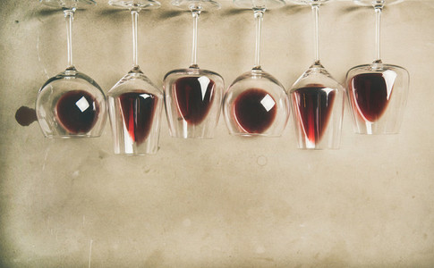 Red wine in different glasses over grey background  copy space