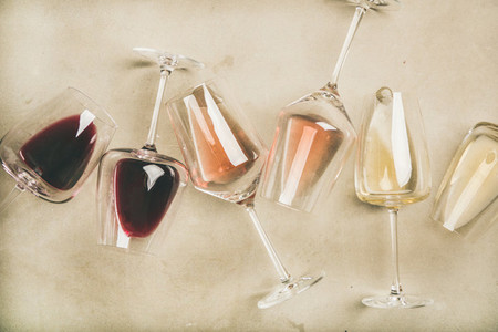 Red rose and white wine in glasses over grey background