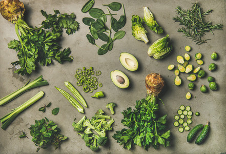Flat lay of whole and cut green vegetables and edible herbs